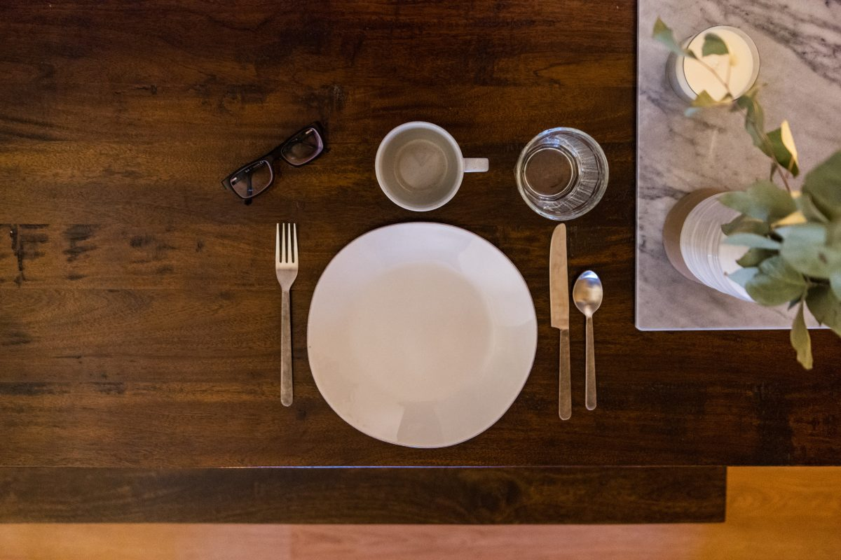 Empty plate, two glasses, silverware, and eyeglasses on a wood table