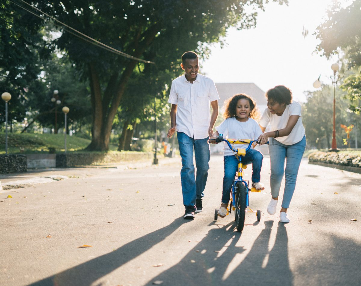 Mother and father helping daughter ride bicycle on the road