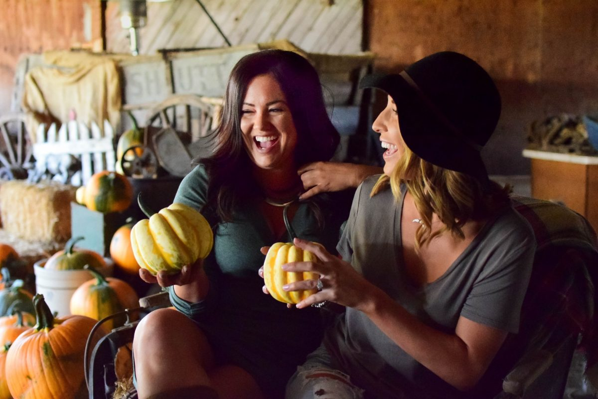 Happy women holding pumpkins and celebrating healthy eating on Thanksgiving