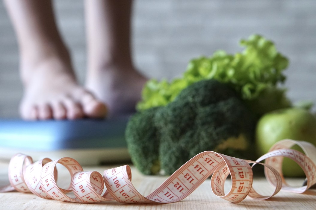 HCG weight loss - woman on scale with measuring tape and vegetables in foreground