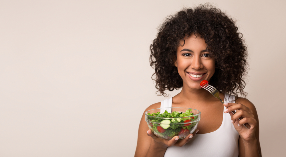 Healthy woman eating salad in intermittent fasting plan