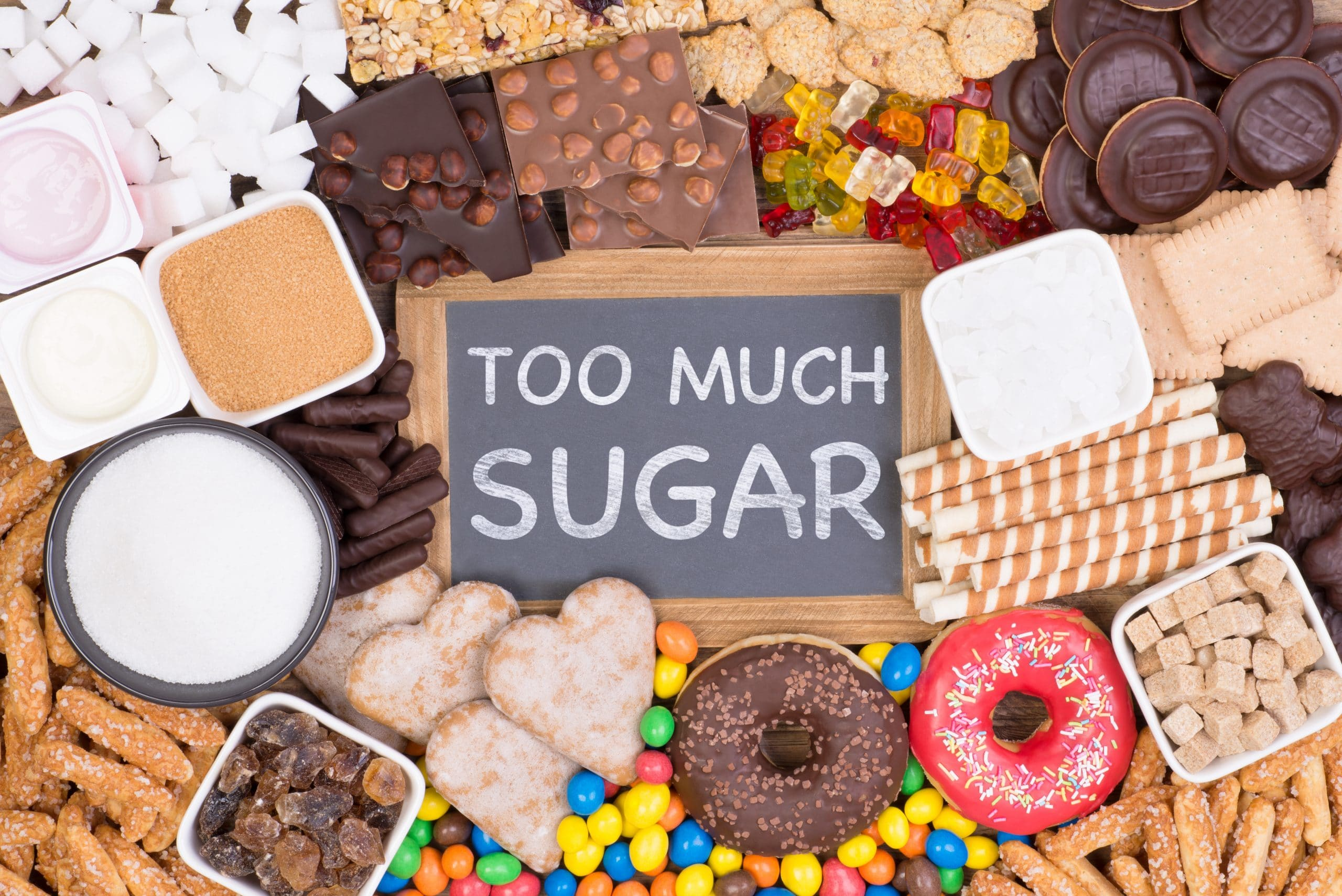sign that says too much sugar and is surrounded by sugary foods