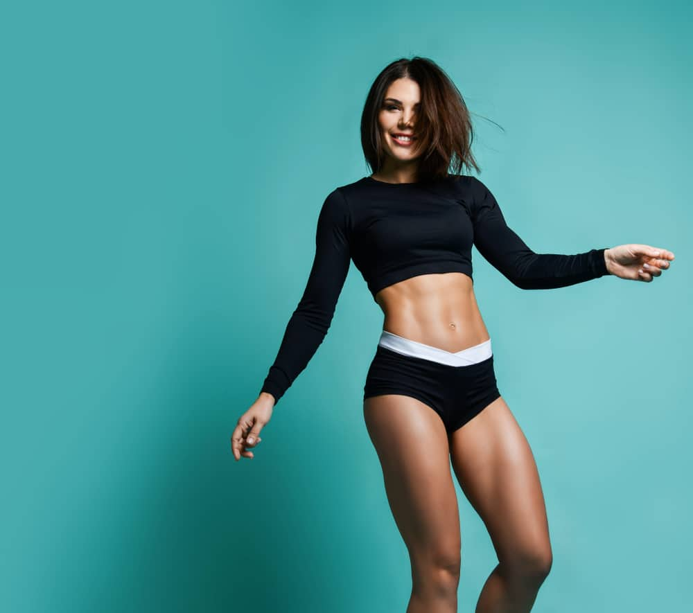 fit woman wearing black crop top with long sleeves and black underpants standing in front of green background