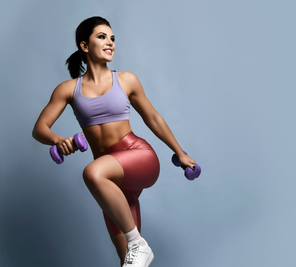 fit woman wearing athletic clothing and holding weights